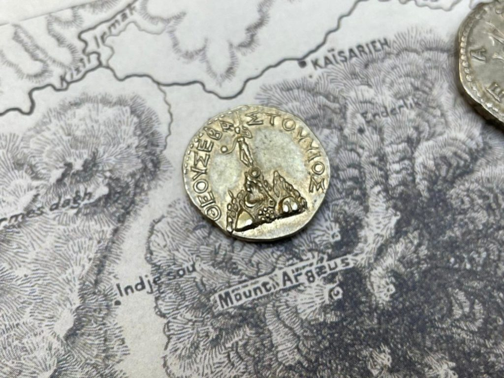 A silver ancient coin featuring Mount Argaeus with the figure of a man standing on top of the mountain. The coin is laid on top of ancient maps featuring the mountain.