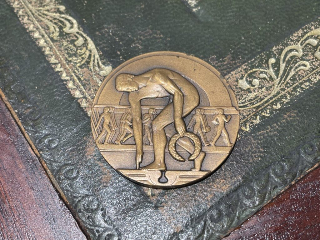 Bronze medal. Obverse of the prototype bronze medal depicting the discus-thrower in art-deco style placed on top of a wood and green leather desk.